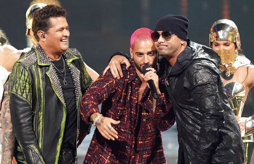 Carlos Vives, from left and Maluma present the excellence award to Wisin at Premio Lo Nuestro at American Airlines Arena on Thursday, Feb. 18, 2021, in Miami.