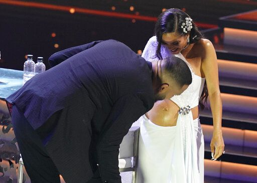 "Raphy Pina kisses Natti Natasha's belly as she walks on stage to accept the award for tropical song of the year for ""La Mejor Version De Mi"" at Premio Lo Nuestro at American Airlines Arena on Thursday, Feb. 18, 2021, in Miami."