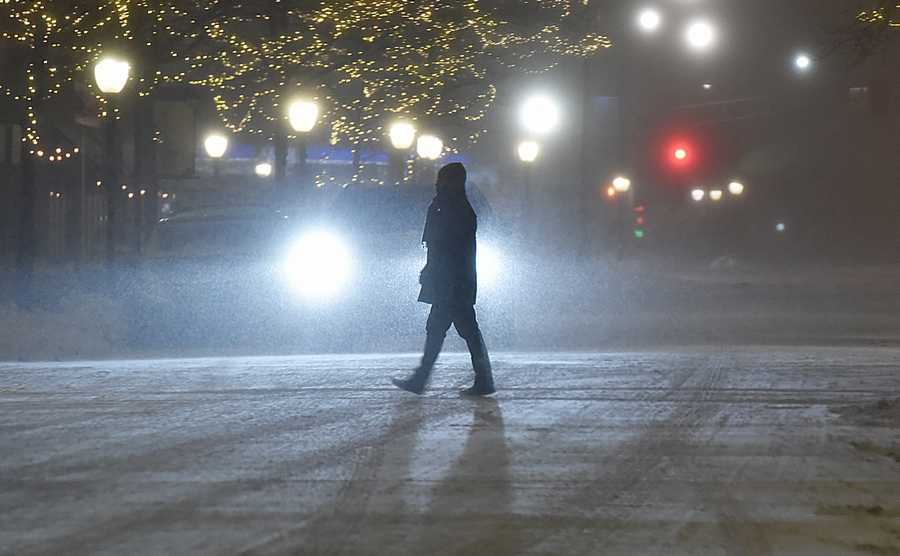 A pedestrian takes small steps in the slippery snow to cross S. Vail Ave. in Arlington Heights Monday night.