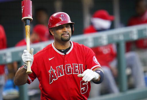 FILE - In this Sept. 12, 2020, file photo, Los Angeles Angels designated hitter Albert Pujols waves to players in the Colorado Rockies dugout in the second inning of a baseball game in Denver. Pujols' wife apparently disclosed that the Angels slugger will retire after the upcoming season, although she later amended her social media post to be less definitive.