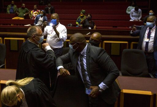 State prosecutor Advocate Billy Downer, left, greets members of the legal team representing former President Jacob Zuma, inside the High Court in Pietermaritzburg, South Africa, Tuesday, Feb. 23, 2021. A South African judge said he will file a criminal complaint against former South African president Jacob Zuma after he staged a dramatic walkout while attending a commission of inquiry looking into corruption during his tenure from 2009 to 2018.