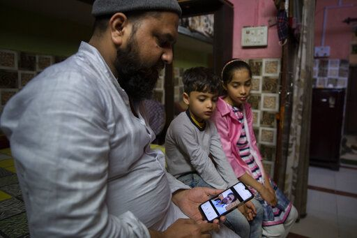 Haroon, holds a mobile phone as his nephew and niece look at the photograph of their father who was shot and killed by their Hindu neighbors during February 2020 communal riots, in North Ghonda, one of the worst riot affected neighborhood, in New Delhi, India, Friday, Feb. 19, 2021. As the first anniversary of bloody communal riots that convulsed the Indian capital approaches, Muslim victims are still shaken and struggling to make sense of their struggle to seek justice.
