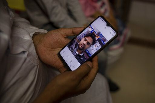 Haroon holds a mobile phone with a photograph of his 32 year-old brother who was shot and killed by his Hindu neighbors during the February 2020 communal riots, inside his home in North Ghonda, one of the worst riot affected neighborhood, in New Delhi, India, Friday, Feb. 19, 2021. As the first anniversary of bloody communal riots that convulsed the Indian capital approaches, Muslim victims are still shaken and struggling to make sense of their struggle to seek justice.