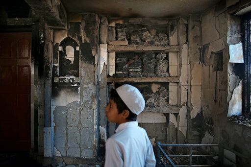 FILE - In this Thursday, Feb. 27, 2020, file photo, an Indian Muslim boy stands inside a mosque burnt in Tuesday's communal violence in New Delhi, India. As the first anniversary of bloody communal riots that convulsed the Indian capital approaches, Muslim victims are still shaken and struggling to make sense of their struggle to seek justice. Many say they have run repeatedly into a refusal by police to investigate complaints made by Muslims against Hindu rioters.