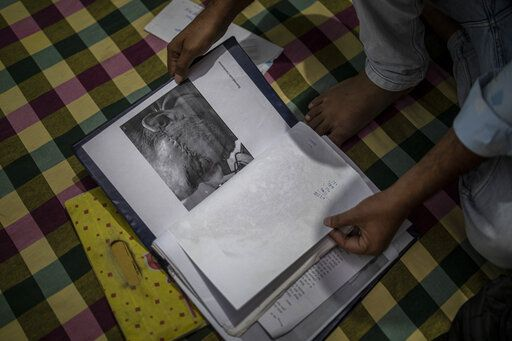Muhammad Nasir Khan, who was shot by a Hindu mob during the February 2020 communal riots, sifts through his legal and medical files inside his home in North Ghonda, one of the worst riot affected neighborhood, in New Delhi, India, Friday, Feb. 19, 2021. As the first anniversary of bloody communal riots that convulsed the Indian capital approaches, Muslim victims are still shaken and struggling to make sense of their struggle to seek justice.