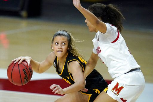 Iowa guard Gabbie Marshall, left, works the floor against Maryland guard Katie Benzan during the first half of an NCAA college basketball game, Tuesday, Feb. 23, 2021, in College Park, Md.