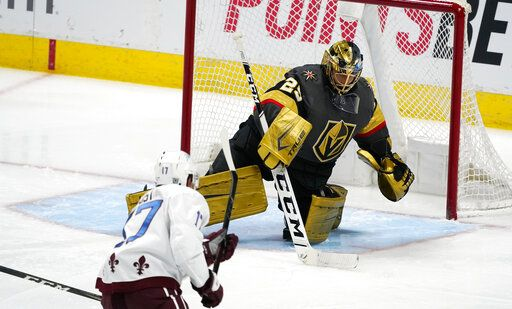 Vegas Golden Knights goaltender Marc-Andre Fleury, back, makes a stick save of a shot by Colorado Avalanche center Tyson Jost in the first period of an NHL hockey game Monday, Feb. 22, 2021, in Denver.