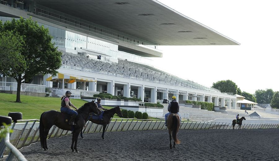 Exercise riders wait in front of the grandstand for their jockeys in 2020 at Arlington Park.