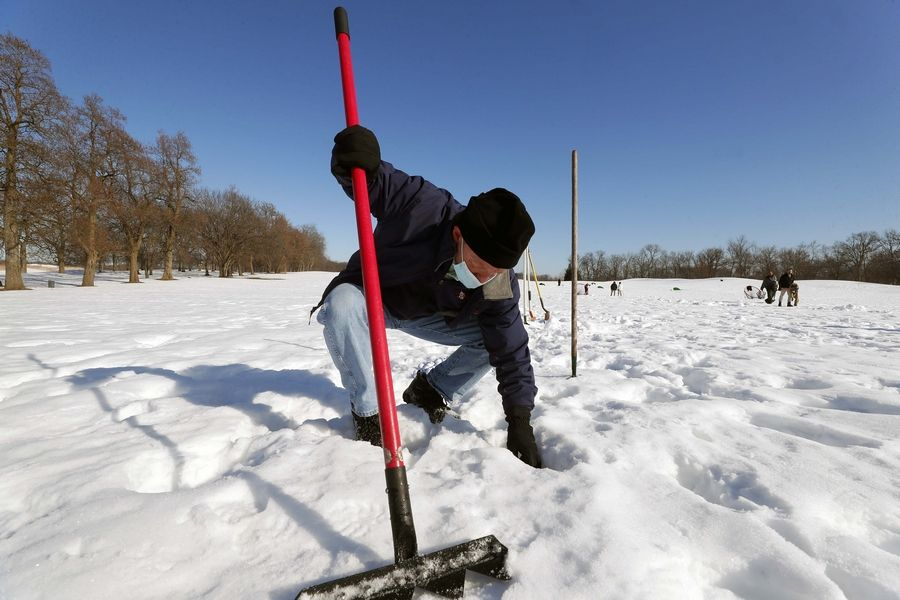 Jeff Reiter, senior manager of communications at Cantigny Park, helps pick up golf balls under deep snow at the Cantigny Golf Academy driving range Thursday in Wheaton.