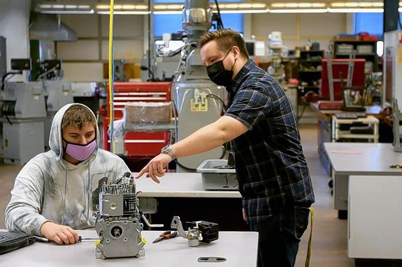 Woodstock High School teacher Austen Luedtke helps freshman Aaron Brohammer in their Orientation into Industrial Technology Transportation and Production class at Woodstock High School on Tuesday, in Woodstock.