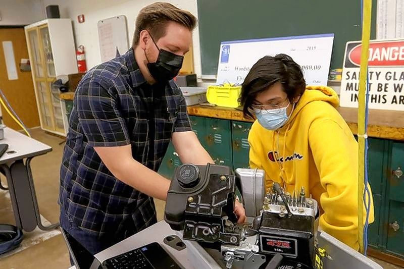 Woodstock High School teacher Austen Luedtke helps sophomore Carlos Garcia in their Orientation into Industrial Technology Transportation and Production class at Woodstock High School on Tuesday in Woodstock.