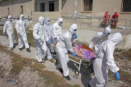 Medical workers in protective suits remove the body of Fatima Abdi, 51, who died from COVID-19 according to her daughter, from a ward for coronavirus patients at the Martini hospital in Mogadishu, Somalia Wednesday, Feb. 24, 2021.
