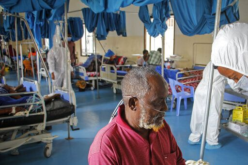 A doctor tends to a patient suffering from COVID-19 in a ward for coronavirus patients at the Martini hospital in Mogadishu, Somalia Wednesday, Feb. 24, 2021.