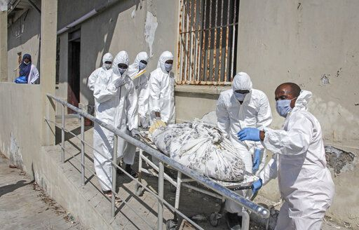 Medical workers in protective suits remove the body of a patient who died from COVID-19 from a ward for coronavirus patients at the Martini hospital in Mogadishu, Somalia Wednesday, Feb. 24, 2021.