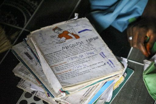 Schoolbooks sit next to Student Masauda Umar, 20, who hid under her bed and managed to escape when gunmen abducted more than 300 girls from her boarding school on Friday, as she recounts her ordeal at her house in Jangebe town, Zamfara state, northern Nigeria Saturday, Feb. 27, 2021. Nigerian police and the military have begun joint operations to rescue the more than 300 girls who were kidnapped from the Government Girls Junior Secondary School, according to a police spokesman.