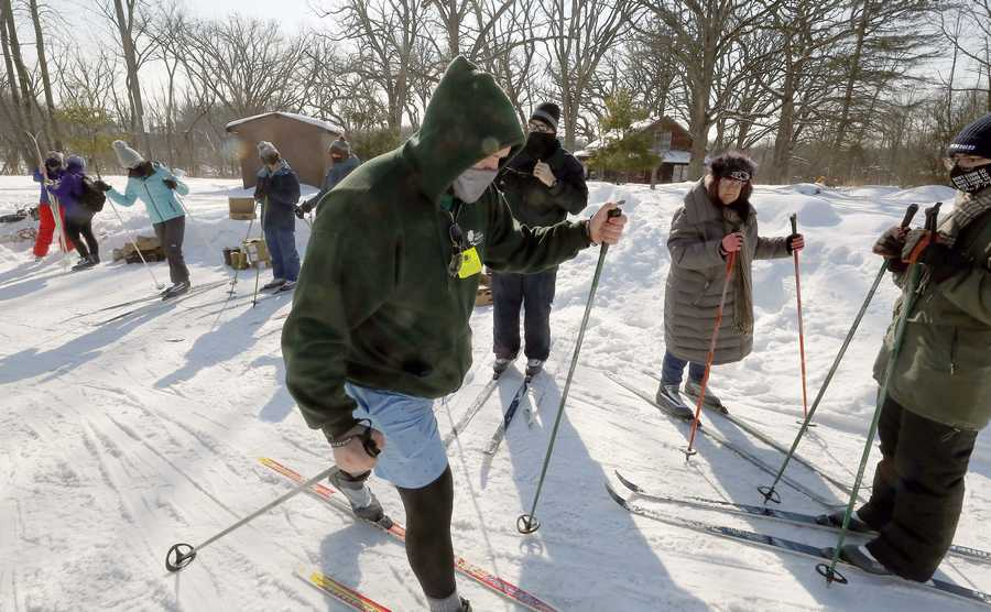 Cook County Forest Preserves' Jonny Brann, center, helps people learn basic cross-country skiing techniques and test out some skis while exploring the trails around Camp Reinberg Saturday, February 20, 2021 in Palatine.