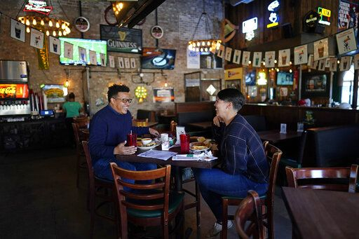 Tasha Arevalo, right, laughs with Joseph Butler while eating at Mo's Irish Pub, Tuesday, March 2, 2021, in Houston. Texas Gov. Greg Abbott announced that he is lifting business capacity limits and the state's mask mandate starting next week.