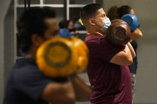 FILE - In this Nov. 24, 2020, file photo, Juan Avellan, center, and others wear masks while working out in an indoor class at a Hit Fit SF gym amid the coronavirus outbreak in San Francisco. Indoor dining, movie theaters and gyms can reopen within 24 hours in San Francisco, an upbeat Mayor London Breed announced Tuesday, March 2, 2021, as California gave the county the go-ahead to open up more of its economy as the rate of coronavirus cases, hospitalizations and deaths declines statewide.