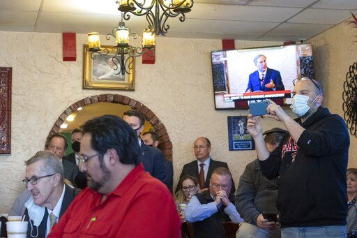 Texas Gov. Greg Abbott delivers an announcement, broadcasted on the TV in the background, as a crowd watches him make it at Montelongo's Mexican Restaurant on Tuesday, March 2, 2021, in Lubbock, Texas. Governor Abbott announced that he is rescinding executive orders that limit capacities for businesses and the statewide mask mandate. (Justin Rex/Lubbock Avalanche-Journal via AP)