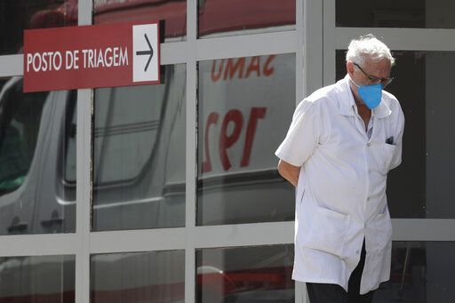 A doctor gets some fresh air as he takes a walk outside the HRAN Hospital in Brasilia, Brazil, Wednesday, March 3, 2021. The number of new COVID-19 cases in Brazil is still surging, with a new record high of deaths reported on Tuesday.