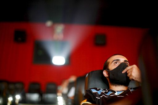 A man watches a movie at a cinema after almost a year of theaters being closed due to the COVID-19 pandemic, in Buenos Aires, Argentina, Wednesday, March 3, 2021.