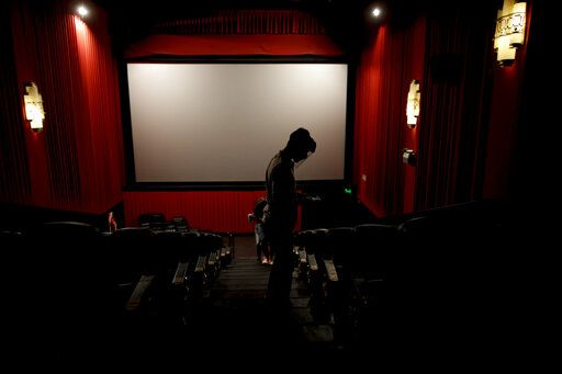 An usher looks for seats at a cinema after almost a year of theaters being closed due to the COVID-19 pandemic, in Buenos Aires, Argentina, Wednesday, March 3, 2021.
