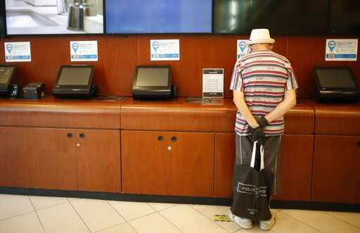 A man prepares to buy a ticket at a cinema after almost a year of theaters being closed due to the COVID-19 pandemic, in Buenos Aires, Argentina, Wednesday, March 3, 2021.