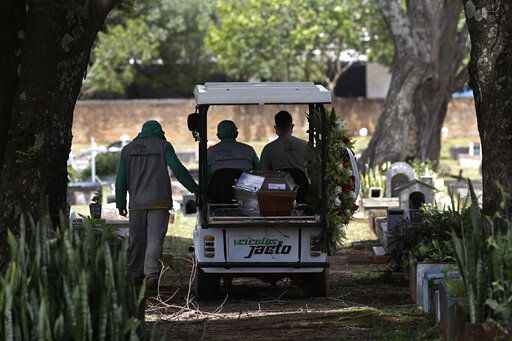 Cemetery workers transport the coffin that contains the remains of Jose Valdelirio believed to have died from the new coronavirus, to a burial site at the Campo da Esperanca cemetery in the Taguatinga neighborhood of Brasilia, Brazil, Wednesday, March 3, 2021. The number of COVID-19 cases in Brazil is still surging, with a new record high of deaths reported on Tuesday.