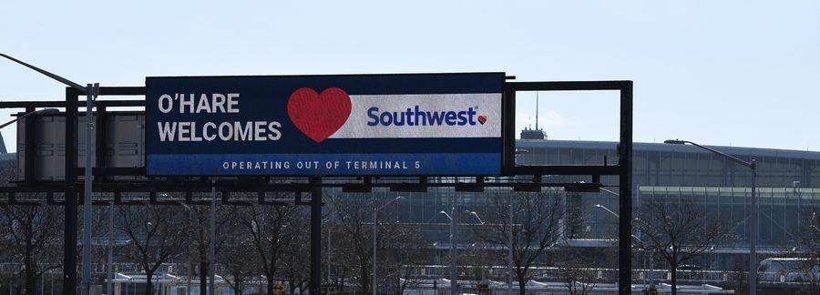Signs tell travelers as they drive into O'Hare International Airport that Southwest Airlines has arrived and is stationed at Terminal 5.