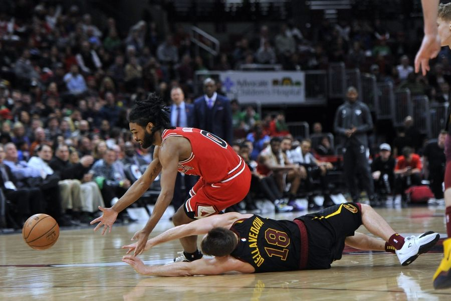 The Bulls' Coby White and Cleveland's Matthew Dellavedova scramble for the ball during the March 10, 2020, game at the United Center. Because of the pandemic, it was the last game the Bulls played for nine months.