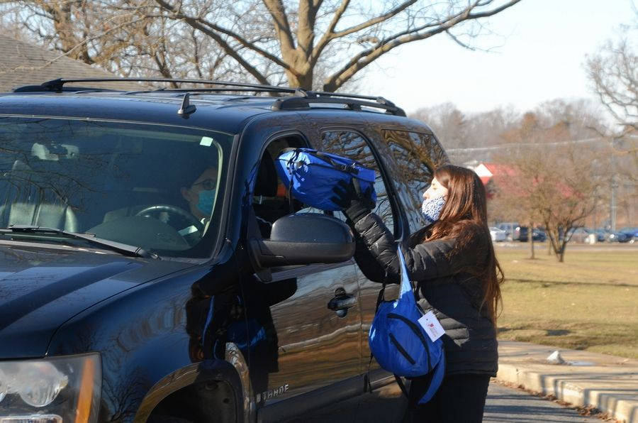 Kayla Hendy, right, Winter Haven, Fla., loads a kids' backpack into a patron's vehicle Saturday, March 6, at Austin Park in Montgomery during a drive-through food giveaway by Aurora Area Interfaith Food Pantry. A fifth distribution will be from 10 a.m. to noon March 20 at Prairie Point Community Park in Oswego.