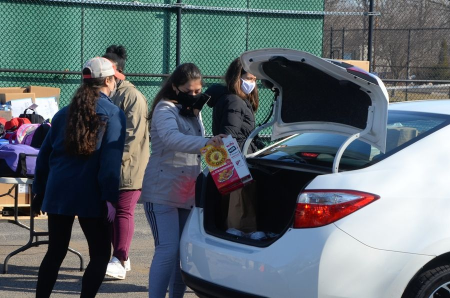 College students on spring break from Southeastern University in Lakeland, Fla., load food into a patron's vehicle Saturday, March 6, at Austin Park in Montgomery. Forty filled backpacks were donated by Family Focus Aurora, a children's advocacy nonprofit.