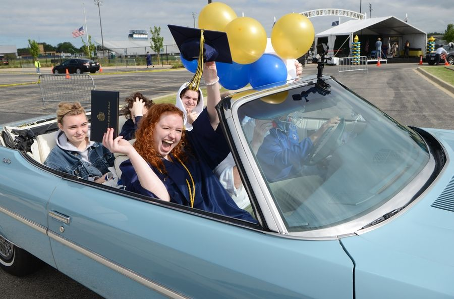 Graduate Jane Mary Bock celebrates while riding in the passenger seat of a 1975 Chevrolet Caprice Classic convertible during the Glenbrook South High School's 2020 graduation ceremony. This year, District 225 plans graduations on campus June 6 and officials are exploring options for smaller ceremonies to give each student an opportunity to walk across a stage and receive a diploma.