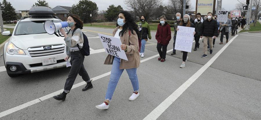 Kaylyn Ahn, 17, left, and Georgeena Mathai, 17, both seniors at Elk Grove High School, lead a march along Algonquin Road in Arlington Heights to protest Asian hate crimes and discrimination.