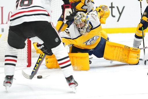 Nashville Predators goaltender Juuse Saros reaches for the puck in the first period of an NHL hockey game against the Chicago Blackhawks Saturday, April 3, 2021, in Nashville, Tenn.