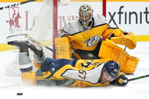 Nashville Predators defenseman Dante Fabbro (57) slides in front of goaltender Juuse Saros to block a shot in the first period of an NHL hockey game against the Chicago Blackhawks Saturday, April 3, 2021, in Nashville, Tenn.