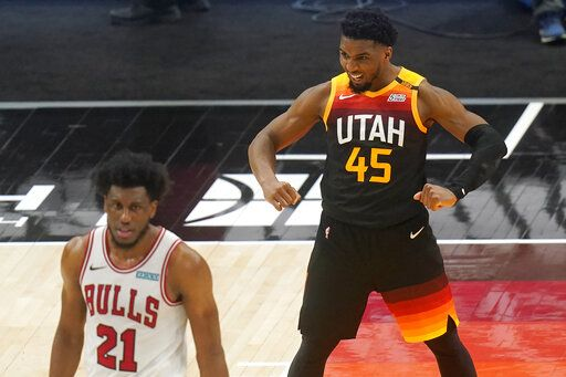 Utah Jazz guard Donovan Mitchell (45) flexes his muscles as Chicago Bulls forward Thaddeus Young (21) walks away in the second half during an NBA basketball game Friday, April 2, 2021, in Salt Lake City.