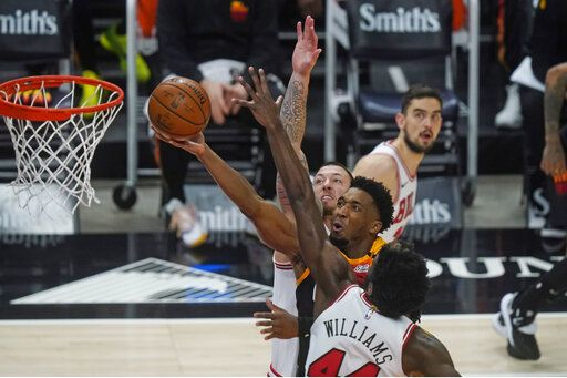 Utah Jazz guard Donovan Mitchell, center, goes to the basket as Chicago Bulls' Daniel Theis, rear, and Patrick Williams (44) defend in the second half during an NBA basketball game Friday, April 2, 2021, in Salt Lake City.