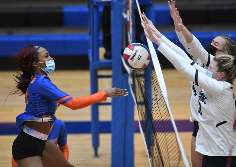 Conant's Danielle Smith and Emily Ytsen block the ball back to Hoffman Estates' Niyah McAllister in a girls volleyball match in Hoffman Estates Monday.