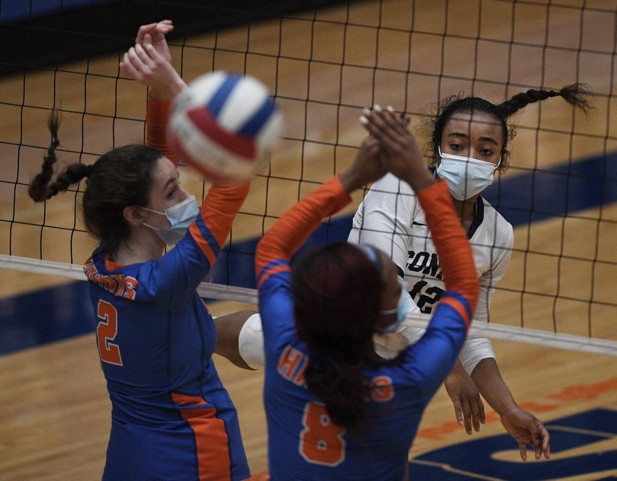 Conant's Farah Cisse hits against Hoffman Estates' Abby Major and Niyah McAllister in a girls volleyball match in Hoffman Estates Monday, April 5, 2021.