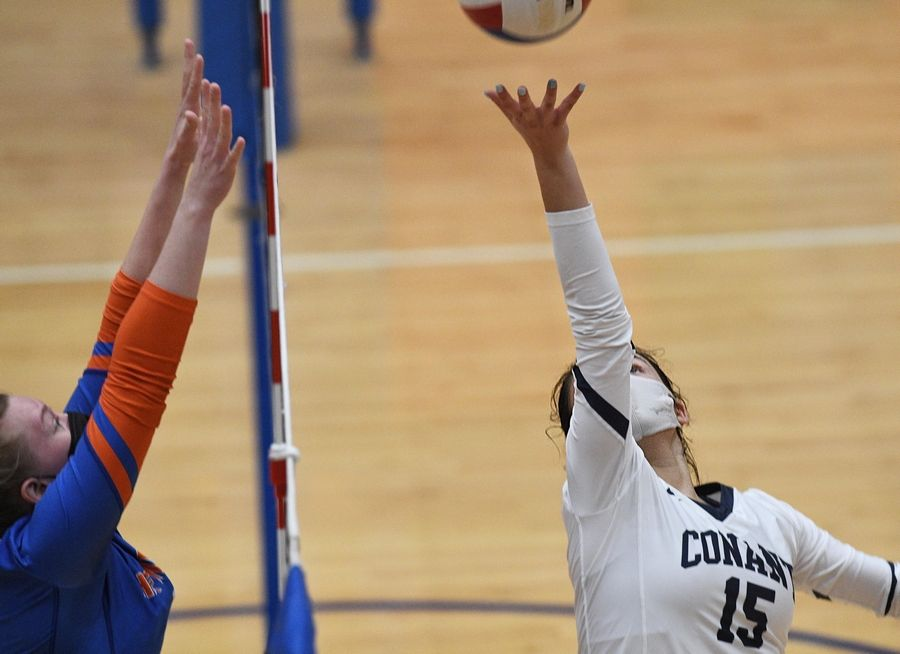 Conant's Gianna Spekta underhands the ball over the net against Hoffman Estates' Sarah Hazenfield in a girls volleyball match in Hoffman Estates Monday, April 5, 2021.