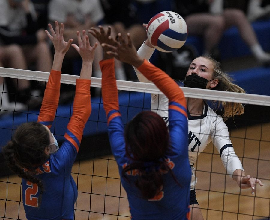 Conant's Danielle Smith hits against Hoffman Estates' Abby Major and Niyah Mcallister in a girls volleyball match in Hoffman Estates Monday, April 5, 2021.