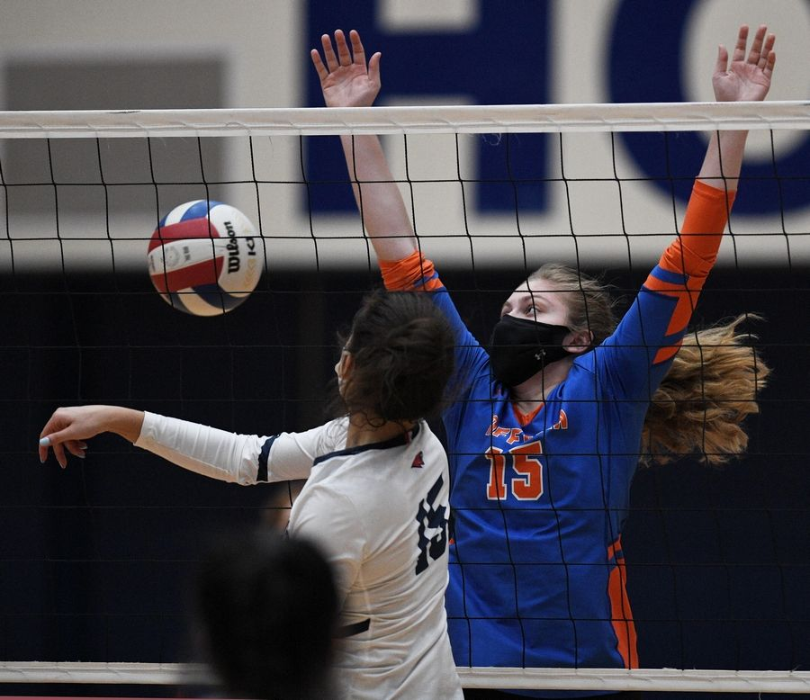 Conant's Gianna Spekta gets the ball past Hoffman Estates' Isabelle Cochran in a girls volleyball match in Hoffman Estates Monday, April 5, 2021.