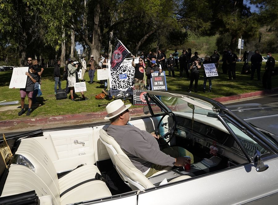 FILE -- In this Feb. 27, 2021, file photo, a driver in his convertible cruises past a small group of anti-COVID-19 vaccine protesters demonstrating at Elysian Park, outside the Dodger Stadium vaccination mass center in Los Angeles. As the world struggles to break the grip of COVID-19, psychologists and misinformation experts are studying why the pandemic spawned so many conspiracy theories, which have led people to eschew masks, social distancing and vaccines.