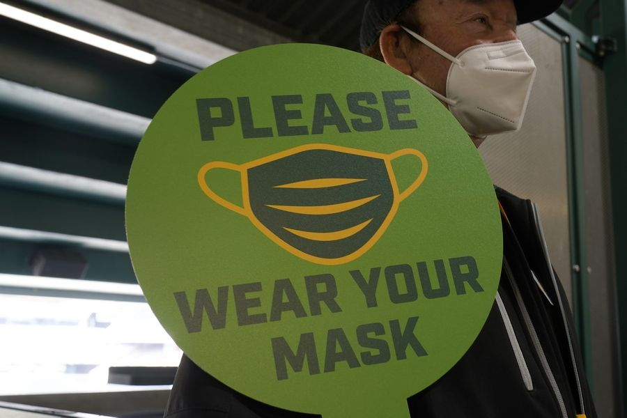FILE -- In this April 3, 2021, file photo, stadium worker holds up a sign for people to wear face masks before a baseball game between the Oakland Athletics and the Houston Astros in Oakland, Calif. As the world struggles to break the grip of COVID-19, psychologists and misinformation experts are studying why the pandemic spawned so many conspiracy theories, which have led people to eschew masks, social distancing and vaccines.
