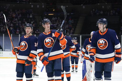 New York Islanders' Brock Nelson, center, leaves the ice with Anthony Beauvillier, left, and Noah Dobson, right, after an NHL hockey game against the Washington Capitals Tuesday, April 6, 2021, in Uniondale, N.Y. The Islanders won 1-0.