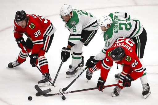 Chicago Blackhawks left wing Brandon Hagel (38) and teammate Ryan Carpenter (22) battle for the puck with Dallas Stars defenseman Andrej Sekera (5) and left wing Jason Robertson (21) during the second period of an NHL hockey game Tuesday, April 6, 2021, in Chicago.