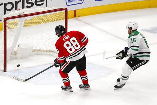 Chicago Blackhawks right wing Patrick Kane (88) scores an empty net goal as Dallas Stars center Joe Pavelski (16) looks on during the third period of an NHL hockey game Tuesday, April 6, 2021, in Chicago. The Blackhawks won the game 4-2.