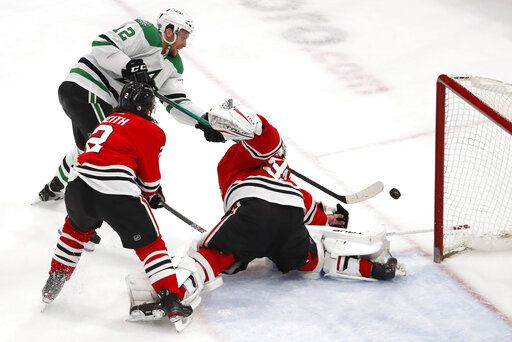 Dallas Stars center Radek Faksa (12) scores a goal past Chicago Blackhawks goaltender Kevin Lankinen (32) and Duncan Keith (2) during the third period of an NHL hockey game Tuesday, April 6, 2021, in Chicago.