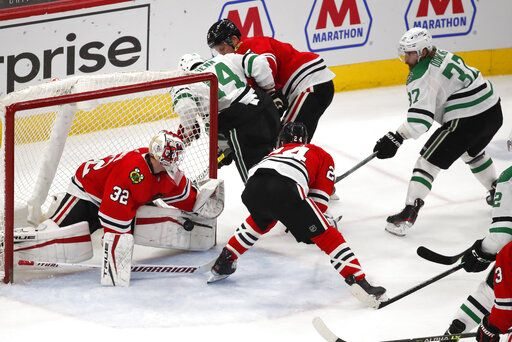 Chicago Blackhawks goaltender Kevin Lankinen (32) stops the shot of Dallas Stars center Justin Dowling (37) during the second period of an NHL hockey game Tuesday, April 6, 2021, in Chicago.